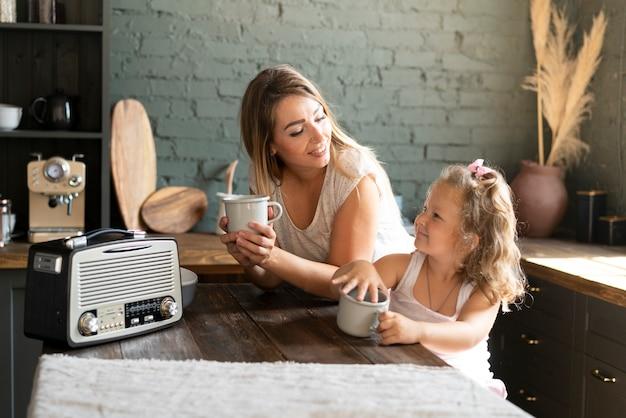 Medium shot moeder en dochter bekers houden Gratis Foto
