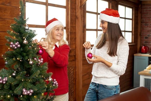 Medium shot moeder en dochter versieren de kerstboom Gratis Foto