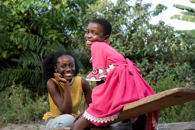 Medium shot smiley afrikaanse vrouw en kind Premium Foto