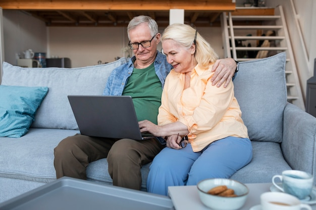 Medium shot smiley gepensioneerd echtpaar met laptop Gratis Foto