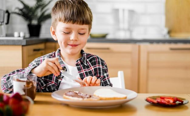 Medium shot smiley jongen met eten Gratis Foto