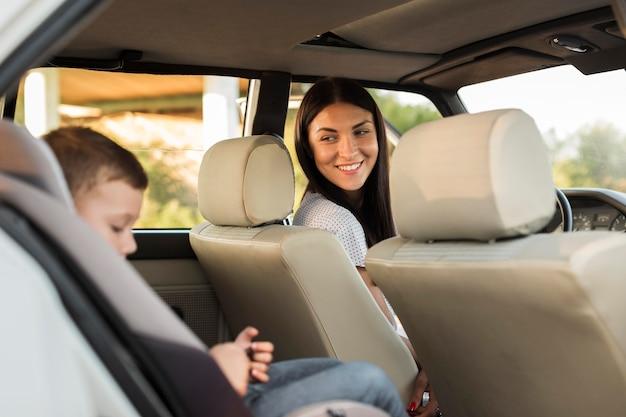 Medium shot smiley moeder kijkt naar kind Gratis Foto