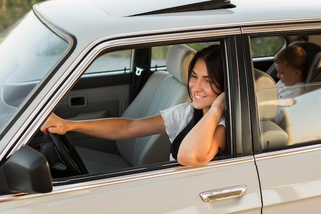 Medium shot smiley vrouw poseren in auto Gratis Foto
