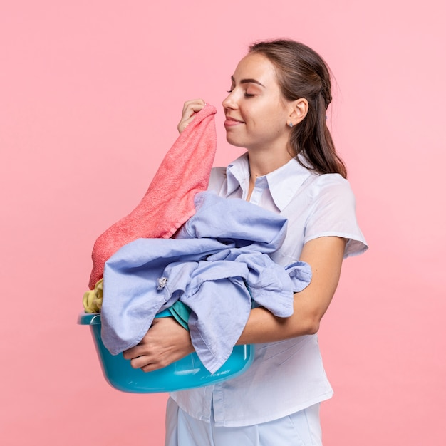 Medium shot smileyvrouw die schone kleren ruikt Gratis Foto