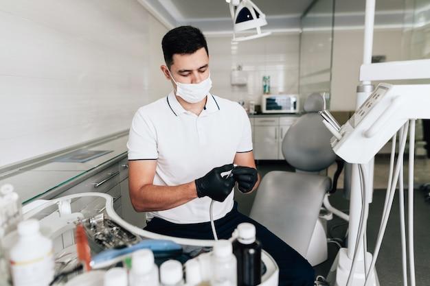 Medium-shot van tandarts die chirurgische apparatuur controleert Gratis Foto