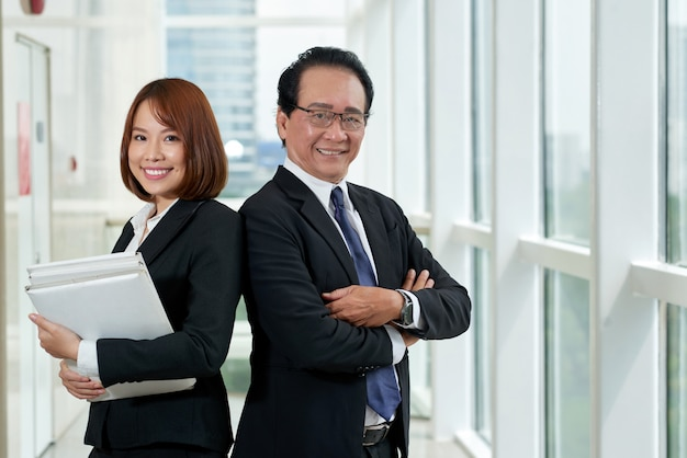 Medium shot van twee aziatische collega's die rug aan rug staan met hun armen over elkaar Gratis Foto