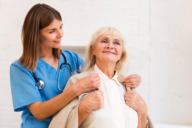 Medium shot verpleegster die oude vrouw met haar jas helpt Gratis Foto