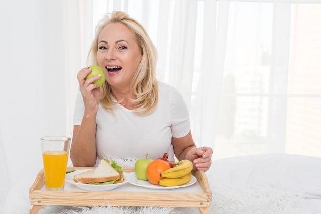 Medium shot vrouw die een appel eet Gratis Foto