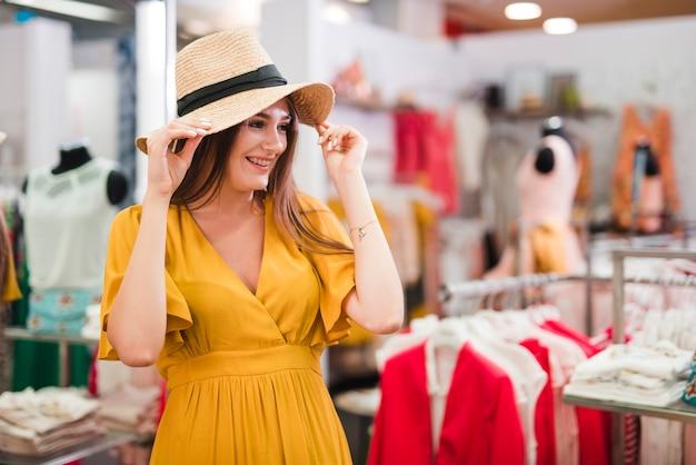 Medium shot vrouw die een hoed uitprobeert Gratis Foto