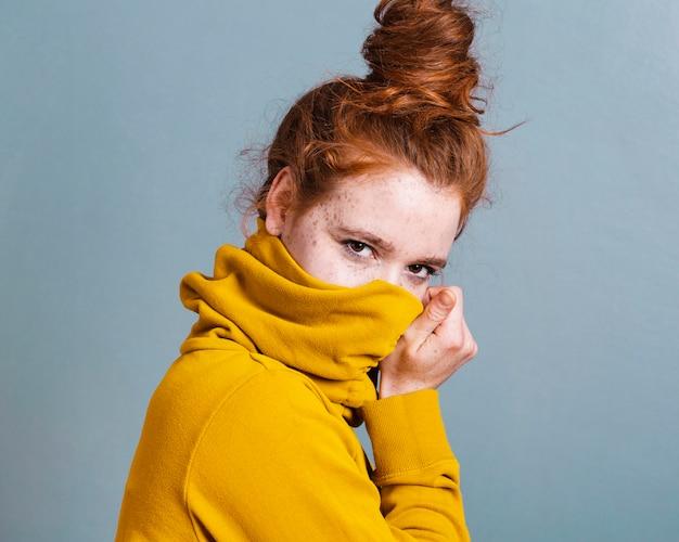 Medium shot vrouw die haar gezicht bedekt met hoodie Gratis Foto