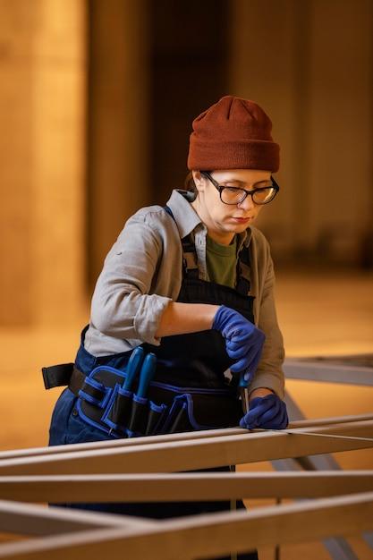 Medium shot vrouw die werkt met een schroevendraaier Gratis Foto
