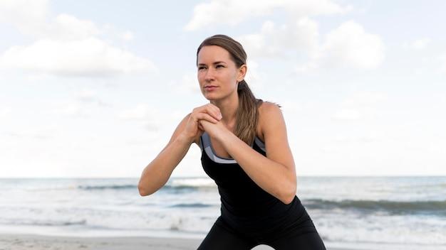 Medium shot vrouw die zich uitstrekt op het strand Gratis Foto