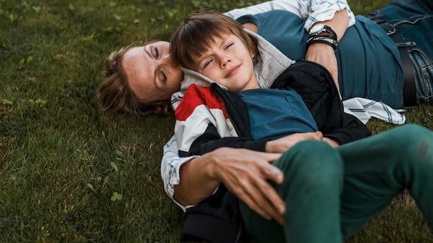 Medium shot vrouw en kind op gras Gratis Foto