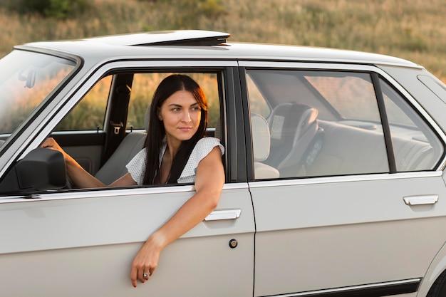 Medium shot vrouw kijkt uit het raam Gratis Foto