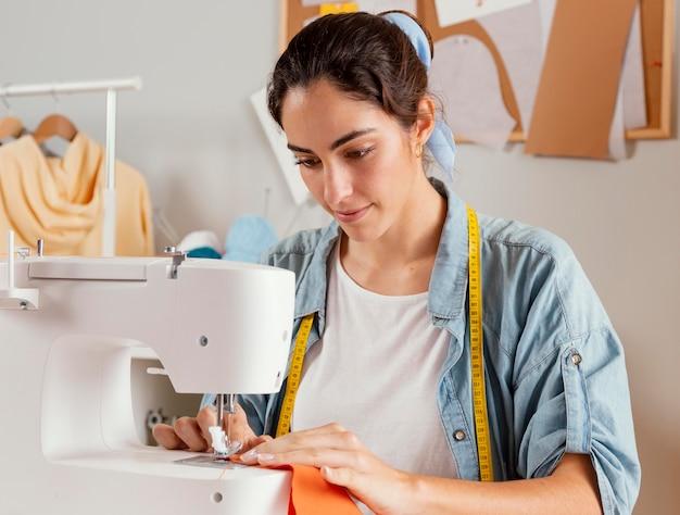 Medium shot vrouw met behulp van naaimachine Premium Foto