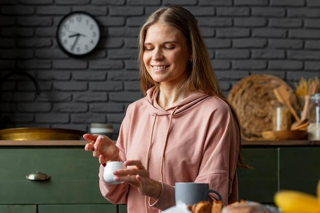 Medium shot vrouw met crème container Gratis Foto