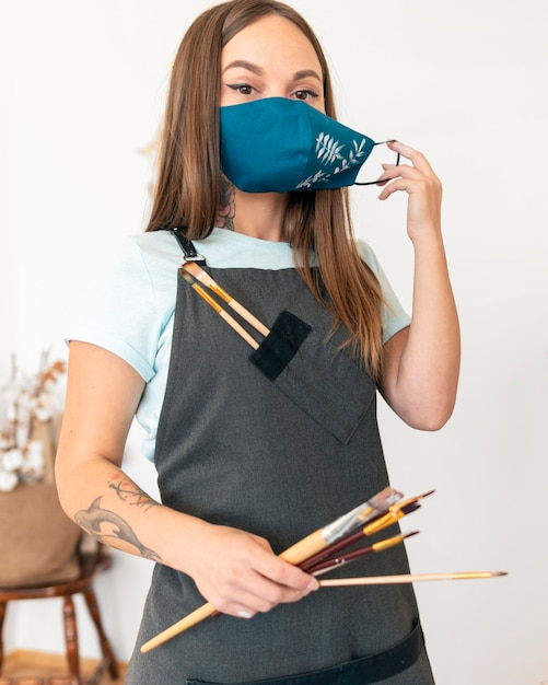 Medium shot vrouw met geschilderd masker Gratis Foto