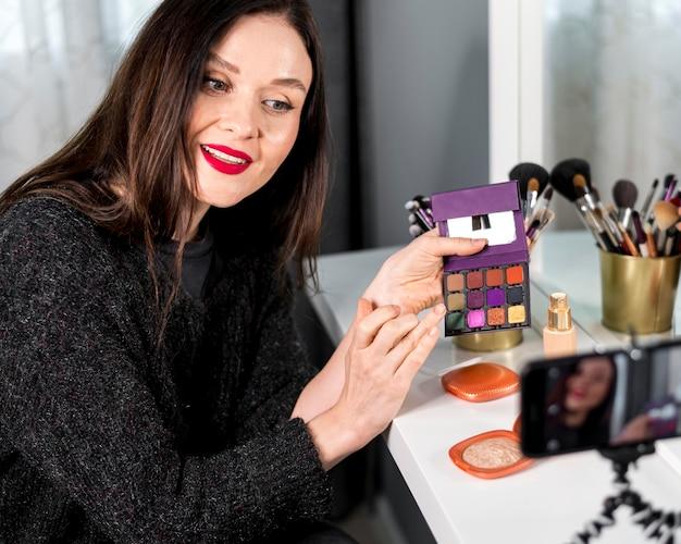 Medium shot vrouw met make-up palet Gratis Foto
