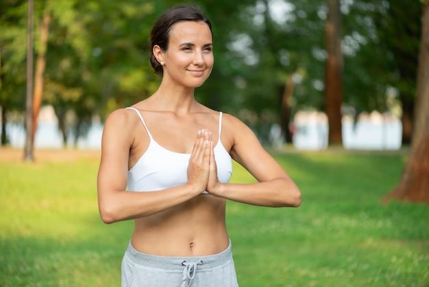 Medium shot vrouw met mediterende arm pose Gratis Foto