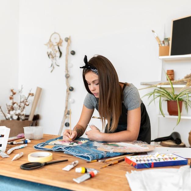 Medium shot vrouw met schilderij penseel Gratis Foto