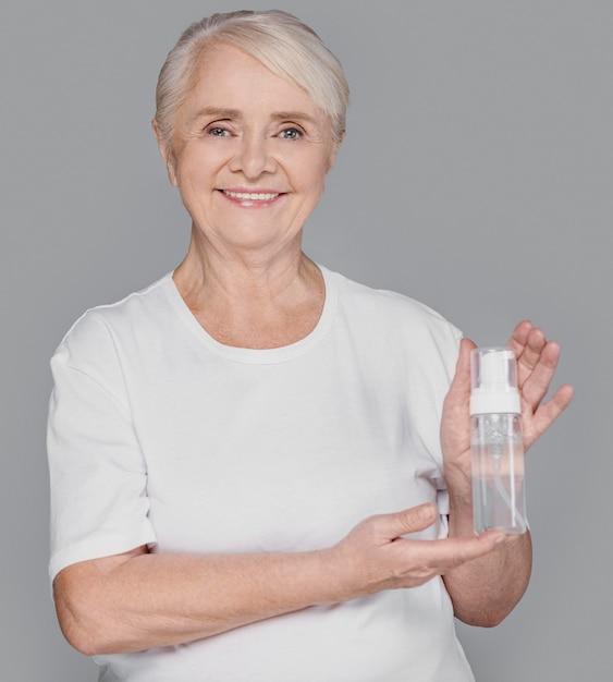 Medium shot vrouw met serumfles Gratis Foto