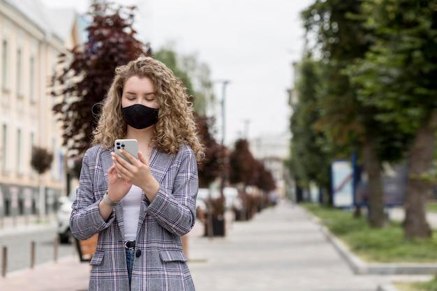 Medium shot vrouw met telefoon buitenshuis Gratis Foto