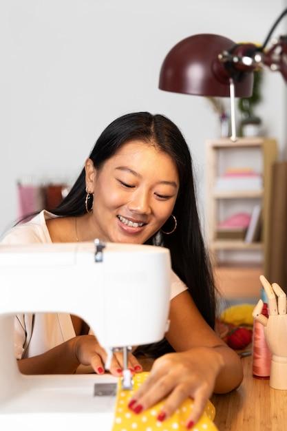 Medium shot vrouw naaien met machine Gratis Foto