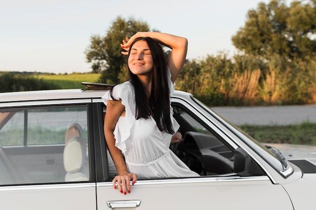 Medium shot vrouw poseren uit het raam Gratis Foto
