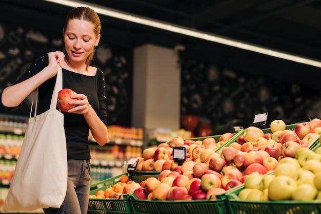 Medium shot vrouw winkelen voor granaatappel Gratis Foto