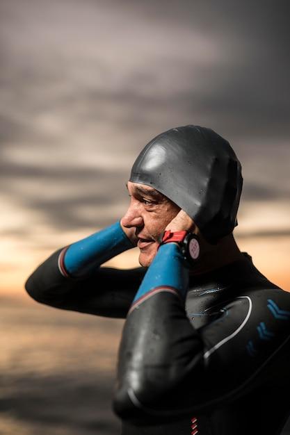 Medium shot zwemmer die een pet opzet Gratis Foto