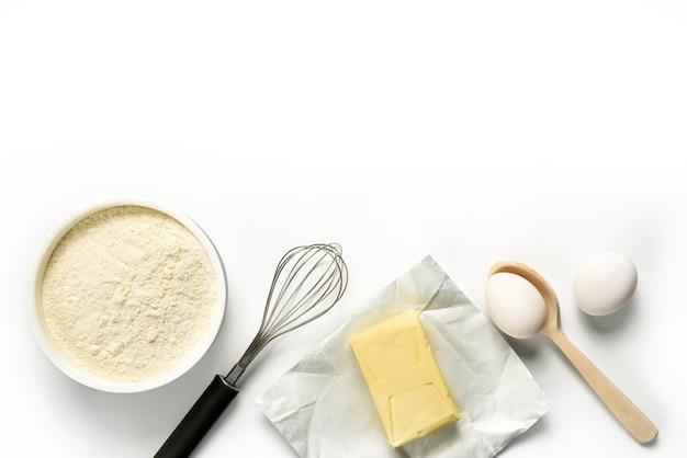 Meel, eieren, boter, garde, lepel geïsoleerd op een witte achtergrond. ingrediënten voor zelfgemaakt bakken op een witte plaat met kopie ruimte. Premium Foto