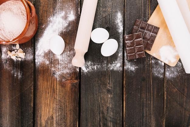 Meel; eieren en chocoladereep met deegrollen en snijplank op tafel Gratis Foto