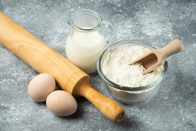 Meel, eieren, melk en deegroller op marmeren oppervlak. Gratis Foto