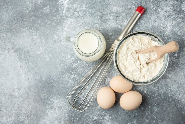 Meel, eieren, melk en snorhaar op marmer. Gratis Foto