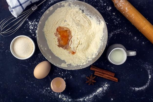 Meel met ei in een metalen kom tussen ingrediënten en keukengerei voor het koken van cake (meel, ei, melk, suiker, deegroller, handdoek) op donkere tafel. het concept van het maken van deeg voor het bakken. detailopname Premium Foto