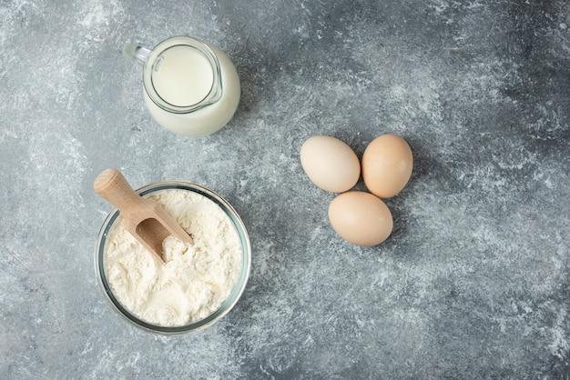 Meel, rauwe eieren en melk op marmer. Gratis Foto