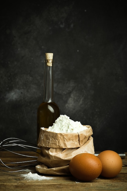 Meel voor het bakken van pizzadeeg brood en pasta op een houten tafel en een donkere achtergrond home cooking concept Premium Foto