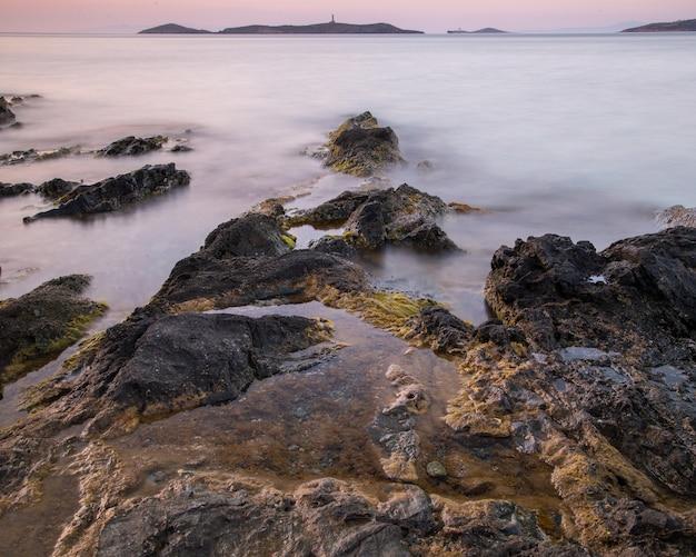 Meer bedekt met rotsen en mist met heuvels op de achtergrond tijdens de zonsondergang Gratis Foto