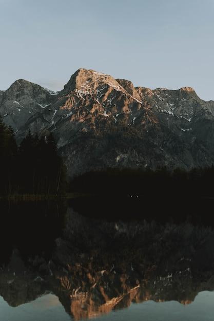 Meer omgeven door bergen met bomen die overdag op het water reflecteren Gratis Foto