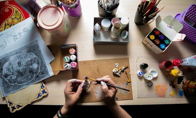 Meester die minifiguren schildert met penseel Gratis Foto