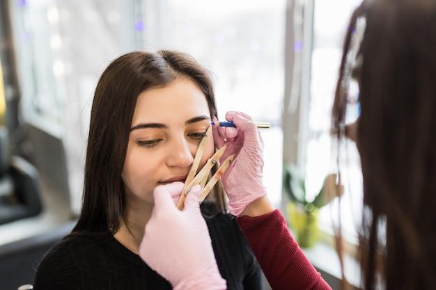 Meester in witte handschoenen werkt aan balck wenkbrauwtechniek in schoonheidssalon Gratis Foto