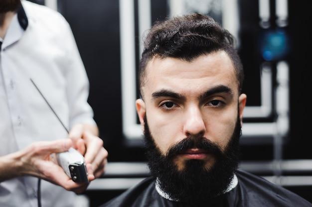 Meester knipt haar en baard van mannen in de kapperszaak, kapper Premium Foto