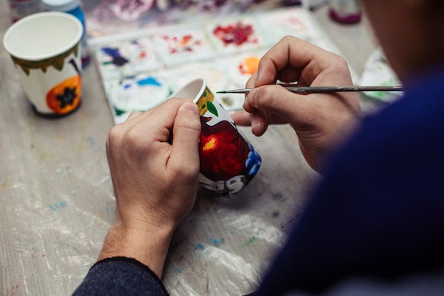 Meester schilderen op een plastic beker Gratis Foto