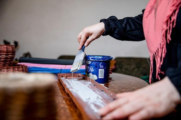 Meester schilderen van een stuk hout in het atelier. hoge kwaliteit foto Gratis Foto