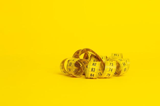 Meetlint op een gele achtergrond. meetlint in de vorm van een spiraal op een gele achtergrond. afslanken en dieet concept, kopie ruimte Premium Foto