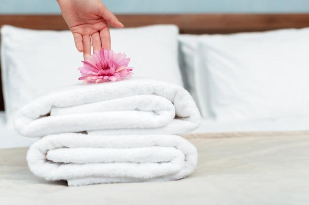 Meid met verse schone handdoeken tijdens huishouden in een hotelkamer Premium Foto