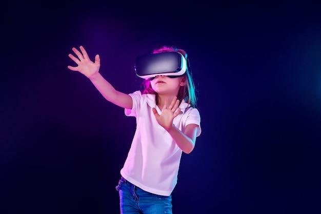 Meisje 7 jaar ervaart vr-headsetspel op kleurrijk. kind gebruikt een gaminggadget voor virtual reality. Premium Foto