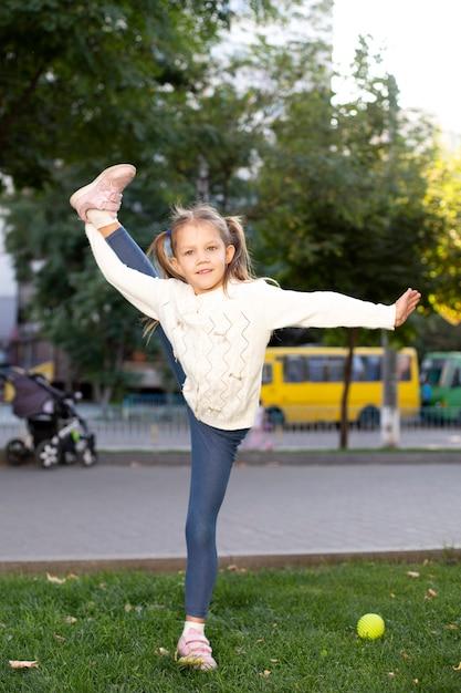 Meisje acrobaat in het park toont bindgaren Premium Foto