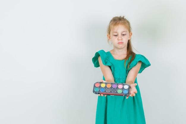 Meisje aquarel verf met penseel in groene jurk te houden en op zoek naar ernstig Gratis Foto