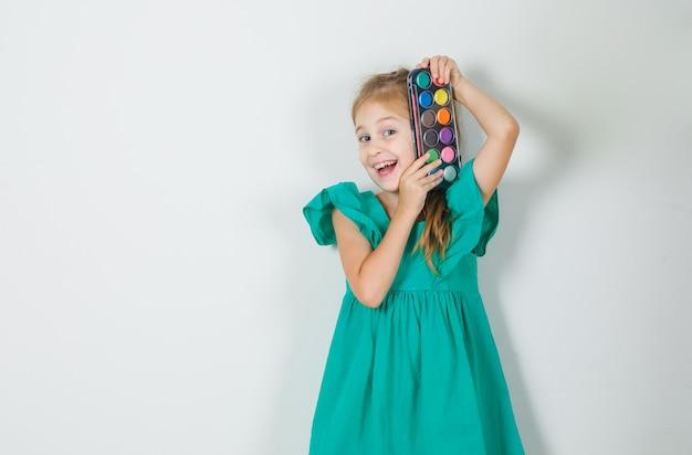 Meisje aquarel verf met penseel in groene jurk te houden en op zoek vrolijk Gratis Foto